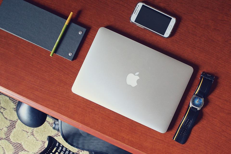 laptop, smartfon i zegarek na biurku